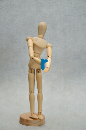 A wooden mannequin holding a letter r