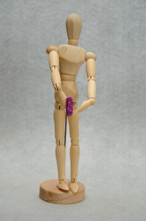 A wooden mannequin holding a letter i