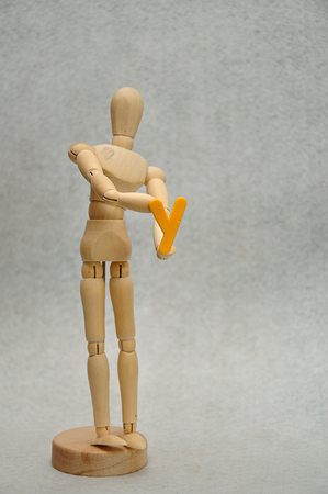 A wooden mannequin holding a letter y Stock Photo