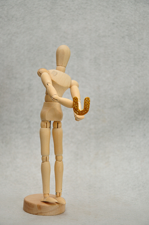 A wooden mannequin holding a letter u Stock Photo