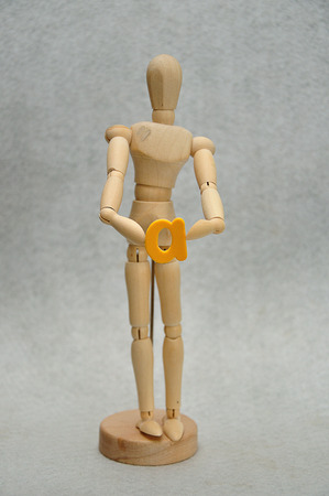 A wooden mannequin holding a letter a Archivio Fotografico