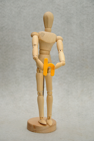 A wooden mannequin holding a letter h