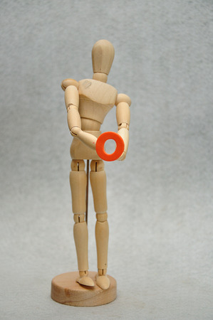 A wooden mannequin holding a letter o