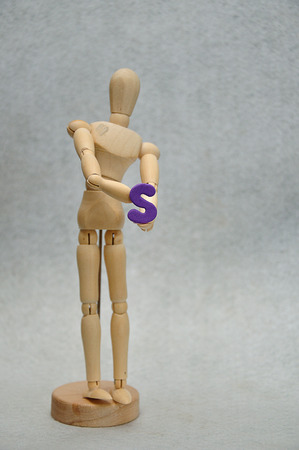 A wooden mannequin holding a letter s