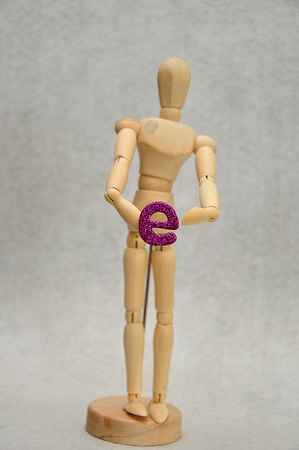 A wooden mannequin holding a letter e Stock Photo