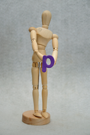 A wooden mannequin holding a letter p