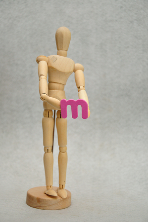 A wooden mannequin holding a letter m