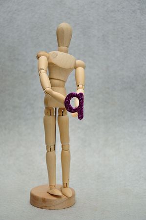 A wooden mannequin holding a letter q