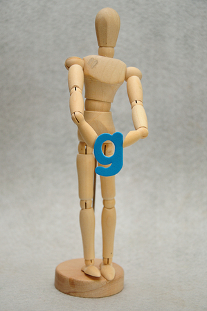 A wooden mannequin holding a letter g
