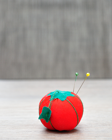 A pin cushion shaped as a red tomato with straight pins Фото со стока