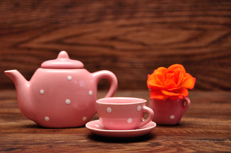 A porcelain spotted tea cup and kettle and an orange rose