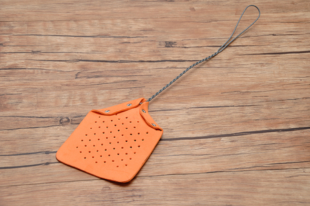 A fly swatter on a wooden background