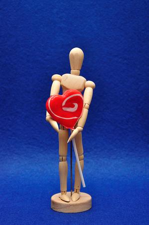 A wooden mannequin holding a heart shape lollipop Archivio Fotografico