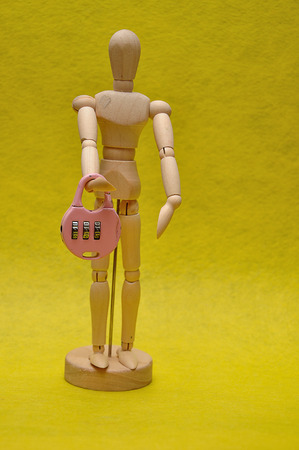 A wooden mannequin holding a combination padlock