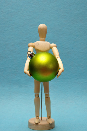 A wooden art mannequin holding a green Christmas bauble