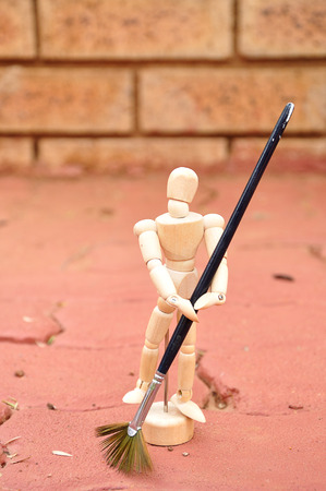 A wooden mannequin with a paint brush as a broom sweeping the paving