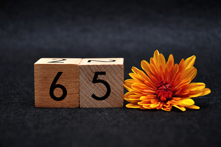 Number sixty five with an orange daisy on a black background