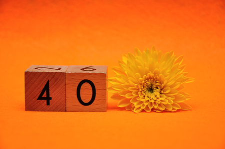 Number forty with a yellow daisy on an orange background