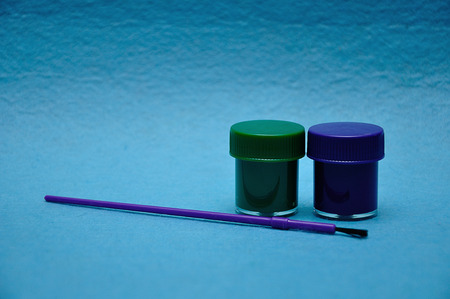 Two pots of paint with a purple paintbrush on a blue background