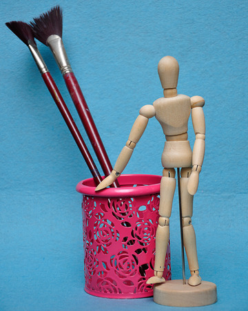 A wooden mannequin display with a pink holder with paint brushes