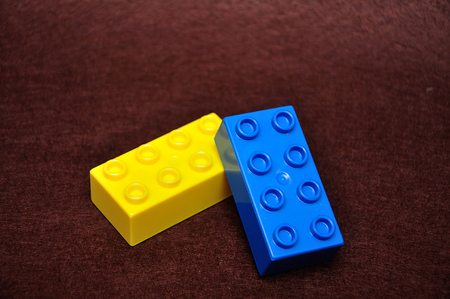 Two colorful building blocks isolated on a brown background Standard-Bild - 122301633
