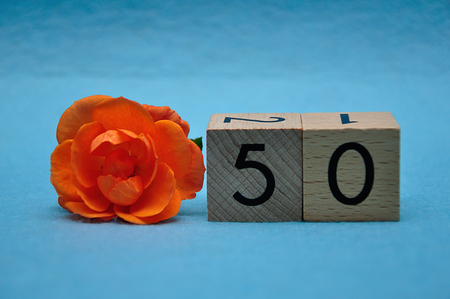 Number fifty with an orange rose on a blue background 写真素材