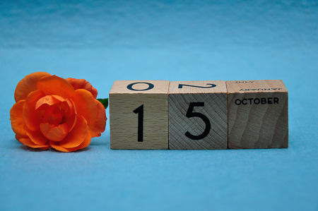 15 October on wooden blocks with an orange rose on a blue background