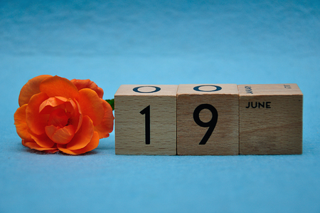 19 June on wooden blocks with an orange rose on a blue background