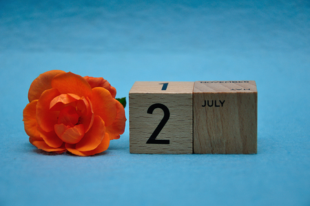 2 July on wooden blocks with an orange rose on a blue background