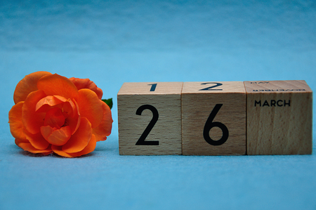 26 March on wooden blocks with an orange rose on a blue background 写真素材