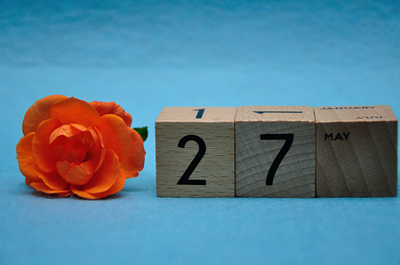 27 May on wooden blocks with an orange rose on a blue background