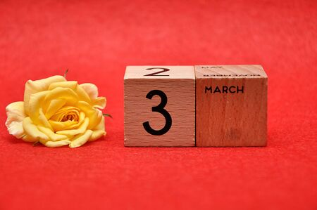3 March on wooden blocks with a yellow rose on a red background