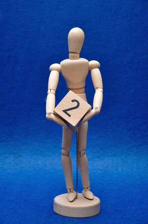 A wooden mannequin with a wooden block with the number two 写真素材