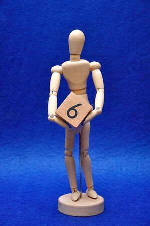 A wooden mannequin with a wooden block with the number six
