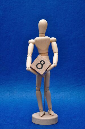 A wooden mannequin with a wooden block with the number eight
