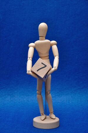 A wooden mannequin with a wooden block with the number seven
