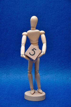 A wooden mannequin with a wooden block with the number five 写真素材