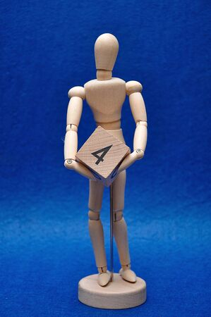 A wooden mannequin with a wooden block with the number four