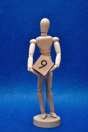 A wooden mannequin with a wooden block with the number nine