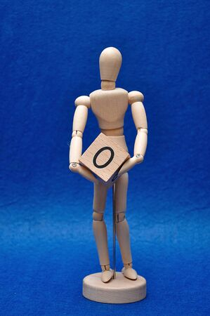 A wooden mannequin with a wooden block with the number zero