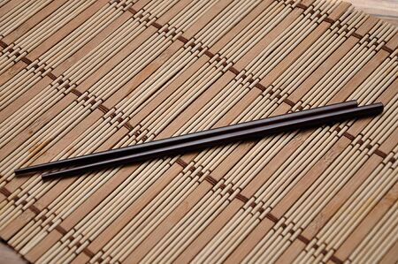 A pair of red chopsticks on a bamboo place mat 写真素材