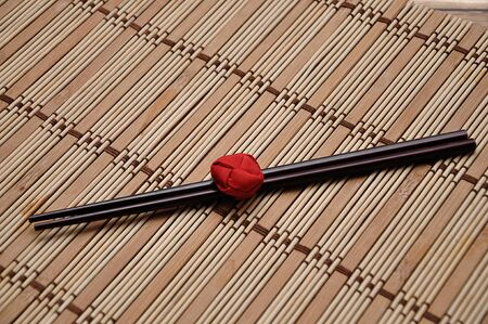 A pair of red chopsticks tied together on a bamboo place mat 写真素材