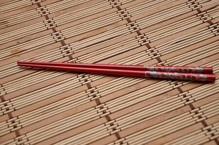 A pair of red chopsticks on a bamboo place mat Stock Photo