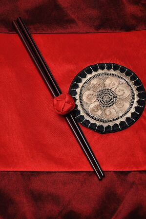 A pair of red chopsticks tied together on a red table cloth 写真素材