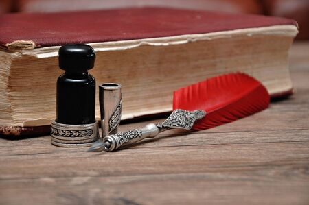 An old pen with a bottle of ink on a wooden table with a red book Stock Photo