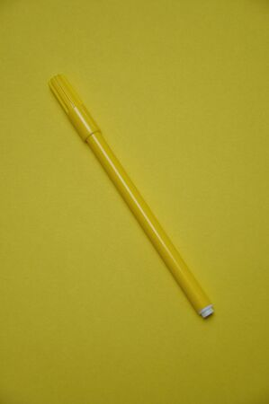 A yellow pen isolated on a yellow background