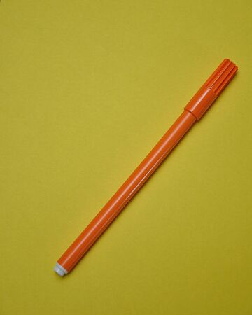 An orange pen isolated on a yellow background