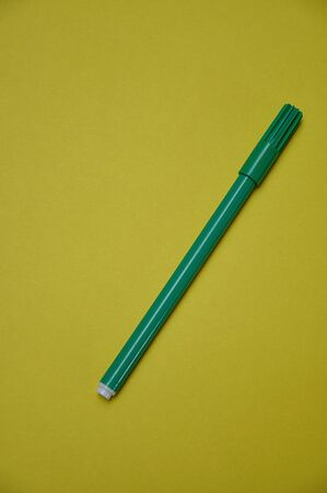 A green pen isolated on a yellow background