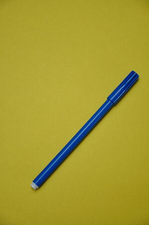 A blue pen isolated on a yellow background