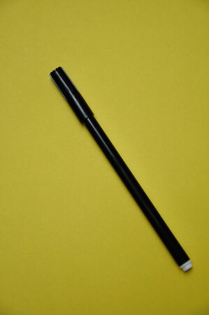 A black pen isolated on a yellow background